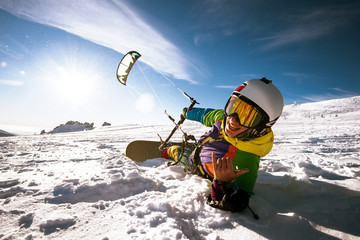 Happy snowboarder lies and holds snowkite