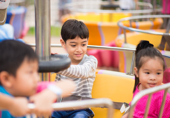 Little boy sitting in marry go round in amusement Theme park