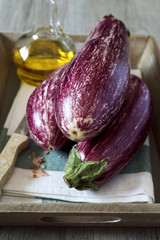Three graffiti eggplants,  pink salt, and olive oil