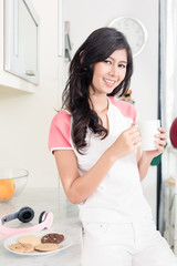 Woman drinking tea or coffee in her Asian kitchen