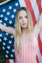 Sexy blonde woman with American flag on background
