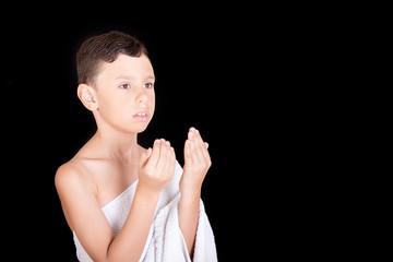 Cute Muslim Kid Praying While Wearing Ihram ( White Traditional Islamic Clothes ) During Hajj