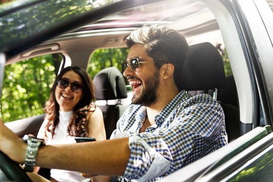 Portrait of young couple driving a car.