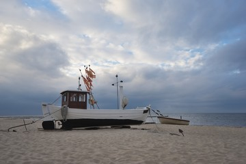Traditional german fishing boat on the beach of Baltic sea in the sunset before storm. Picture taken in East Germany on the Usedom island in the evening in summer, waiting for morning to fish herings.