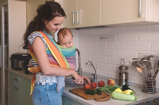 Young mom cooking in the kitchen with the baby. Vegetarian healthy food. Healthy food breastfeeding mothers.