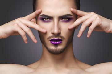 Gay. Pretty sensual fashion man with art makeup and beard.