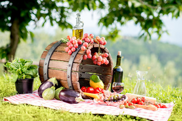 Lots of tasty italian food on the napkin and wooden barrel outdoors in the countryside with tree on the background