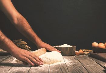 Wall Mural - Men hands roll out dough close up