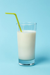 Fresh glass of milk with Straw, on blue background