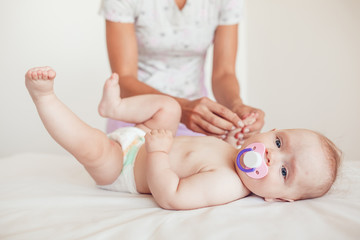 Woman doing exercises and massage the baby