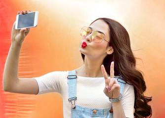 Beautiful woman taking photos on smartphone self-portrait.