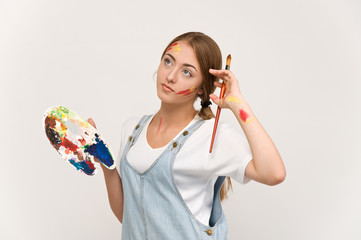 pretty young artist holding a palette and brushes.