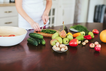woman in a home clothes prepares vegetarian salad in the kitchen. only hands
