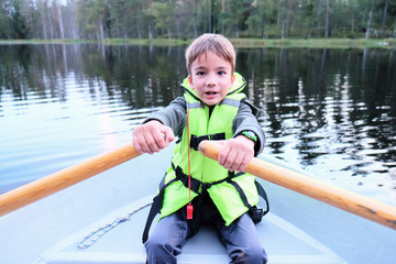 child on a boat at forest lake