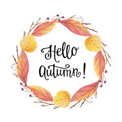 Hello autumn watercolor round frame with colored leaves and hand lettering.