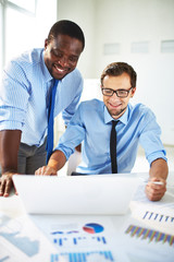 Smiling African-American businessman in shirt and necktie standing beside pleased Caucasian business partner showing something on laptop in office with charts and diagrams laying on table.
