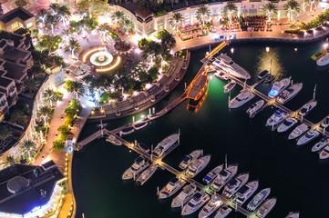 Amazing colorful dubai marina fountain and yacht dock during night. Beautiful sidewalk among tallest skyscrapers of the world. Dubai marina, United Arab Emirates.