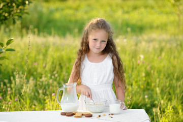 Cute little girl pouring milk and making cereal breakfast outdoor summer
