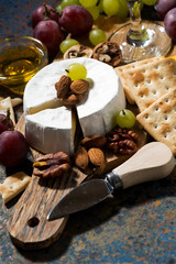 snacks and camembert cheese on a dark background, vertical