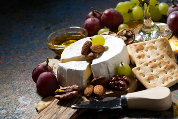 snacks and camembert cheese on a dark background, closeup
