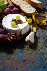 snacks and camembert on dark background, vertical