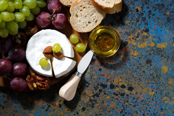 snacks and camembert on dark background, top view