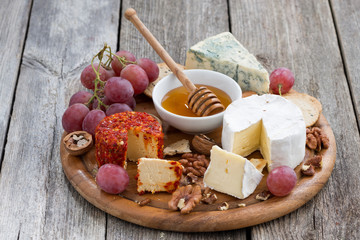 soft cheeses and snacks on a wooden background