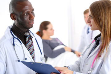 Two doctors share and discuss important document on clipboard pa
