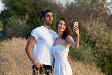 Young attractive couple taking a selfie in nature