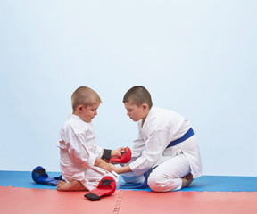 Two karate athlete to dress overlays on hands