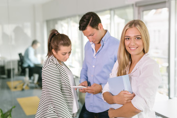 Portrait of an attractive young woman  in an office with colleagues in the background