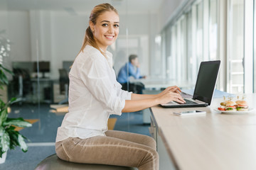 Business woman working on laptop in office while sitting on pilates ball