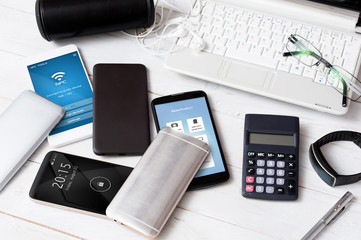 High-end smartphones scattered on the white wooden desk.