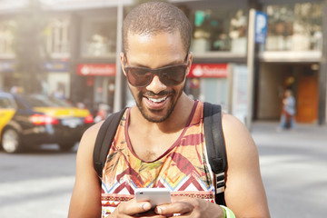 Young attractive African man looking happy and cheerful holding cell phone receiving good news while messaging with his friends via social networks. Black man in shades having fun chatting online