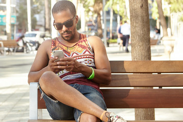 Outdoor portrait of black hipster student on summer day sitting on bench using his Internet-enabled mobile phone, texting message to his friends to invite them to join him, wearing trendy sunglasses