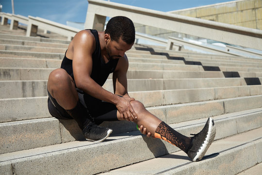 Handsome black runner with muscular athletic body holding his le