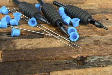 Tattoo needles on wooden background. Stock image macro.