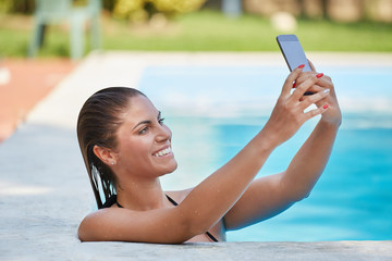 young woman taking a selfie on swimming pool