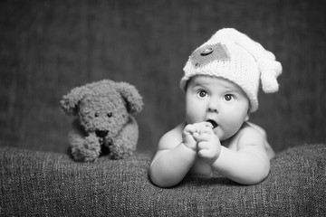 cute curious baby with an open mouth and a teddy bear