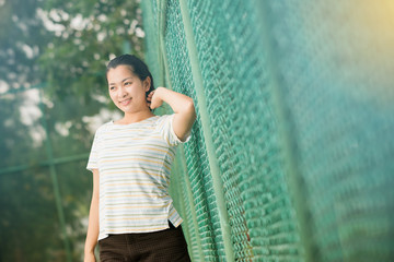 Asian female relax and smile standing on tennis court
