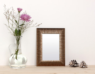 Small bronze frame mockup. Front view. Flowers in a vase and sea shells.