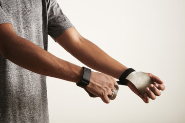 Young athlete closing velcro straps on cross fitness leather hand protectors, shot of hands and torso only against off-white background