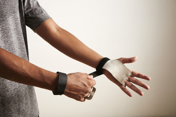 Hands and torso of young African American athlete wearing gray shirt putting on cross fitness leather hand protectors against off-white background