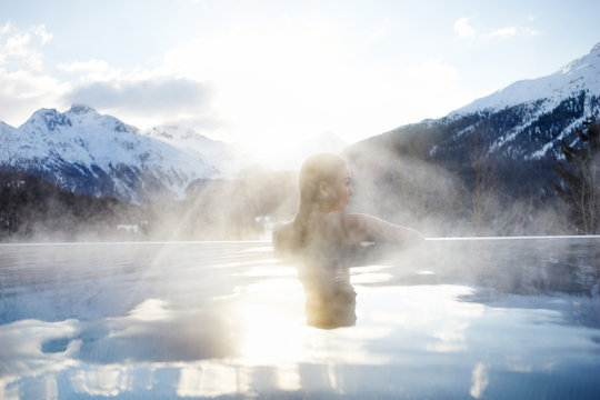 girl in infinity pool in front of mountains