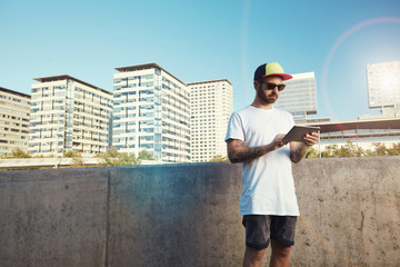 Surprised looking young man with beard and sunglasses wearing a plain white t-shirt reading something on his tablet standing next to a gray concrete wall in a city.