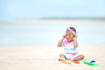 baby girl playing with beach toys at the beach