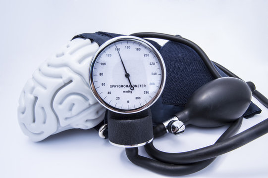 The figure of the human brain enveloped sphygmomanometer cuff with bulb (pear) and dial showing high blood pressure. Concept high brain or increased (raised) intracranial pressure (hypertension)