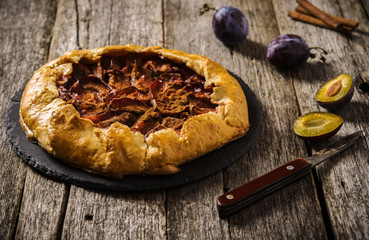 Homemade Rustic Plum Tart with cinnamon, galette on a rough wooden background. Selective focus