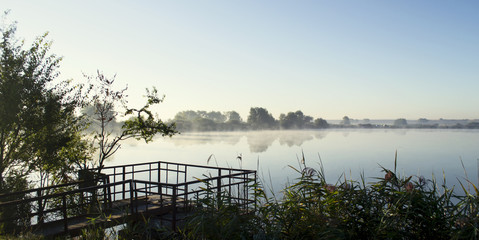 Misty sunrise over a lake summer morning