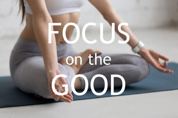 "Beautiful young woman working out in loft interior, doing yoga exercise on blue mat, Sitting in Ardha Padmasana, Half Lotus Pose, meditating, close-up. Motivational phrase ""Focus on the good"""